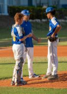 Coach Luis Leal confers pitcher Anthony Ross and catcher Cole McDaniel.