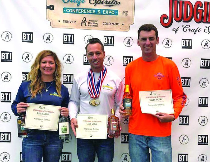 Islamorada Distillery wins big for the Keys at the American Distilling Institute - A group of people posing for the camera - Islamorada