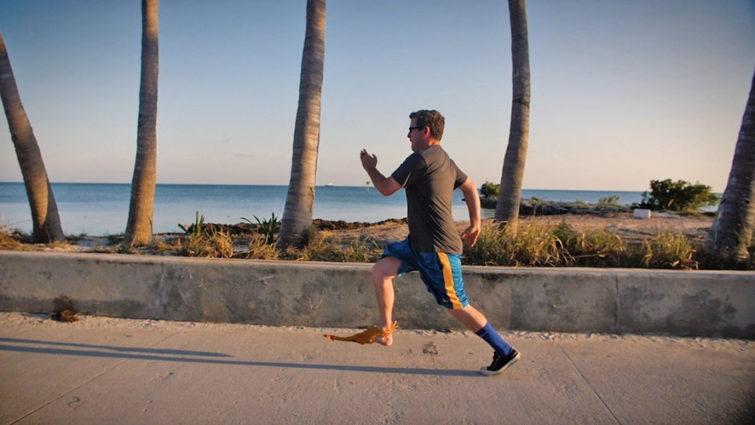 Weekly Interview with local celeb and rubber chicken aficionado Can Billings! - A man carrying a surf board on a beach - Cow Key