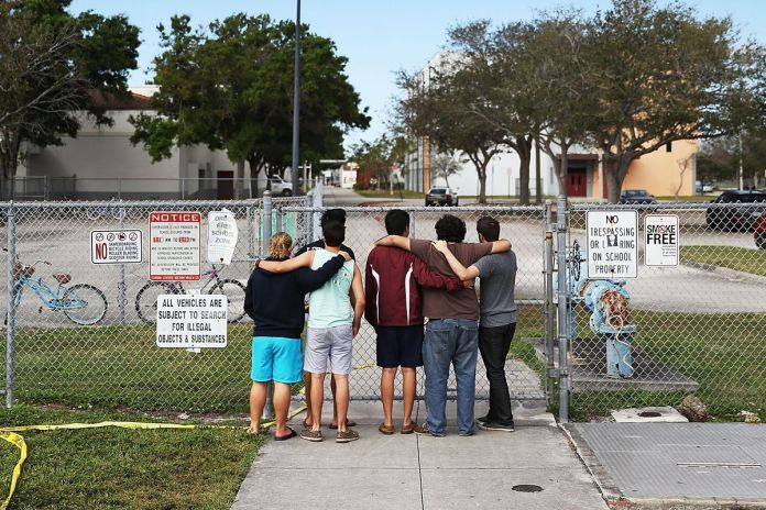 How local schools are facing the surge of national violence - A group of people standing on a sidewalk - Gun violence