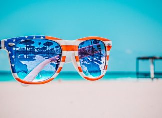 How to best Honor Memorial Day? Thoughts on the holiday from our Publisher, Britt Myers - A blue and yellow sunglasses taking a selfie - Independence Day