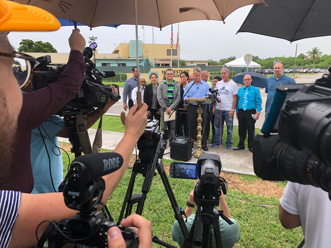 Ministers talk about unaccompanied minors in Homestead facility - A group of people sitting at a table with a umbrella - Florida Keys