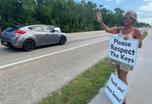 Mom-daughter duo sending positive message to motorists - A person holding a stop sign on the side of a road - Car
