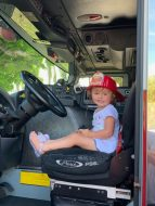 This little future fire fighter gets the feeling of riding in the big red truck.