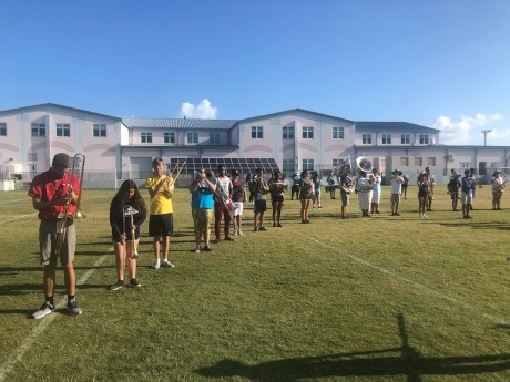 Putting the Band Back Together – KWHS Marching Band prepares for the field - A group of people standing on top of a grass covered field - Team