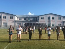 Putting the Band Back Together – KWHS Marching Band prepares for the field - A group of people playing frisbee in front of a building - Musical ensemble