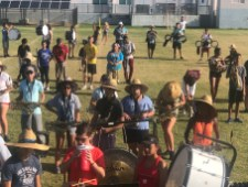 Putting the Band Back Together – KWHS Marching Band prepares for the field - A group of people standing in front of a crowd - Marching band