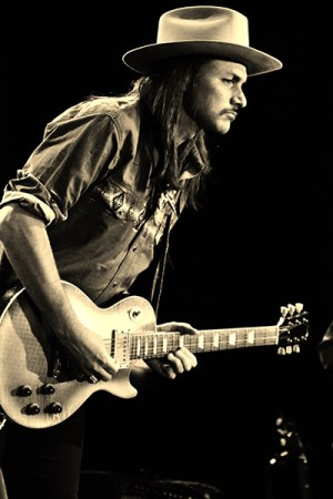 Allman Betts Band Plants New Roots - A person holding a guitar - Devon Allman