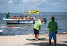 GOLFIN' CONCH STYLE – Funds raised for school, community programs - A group of people standing on top of a sandy beach - Beach