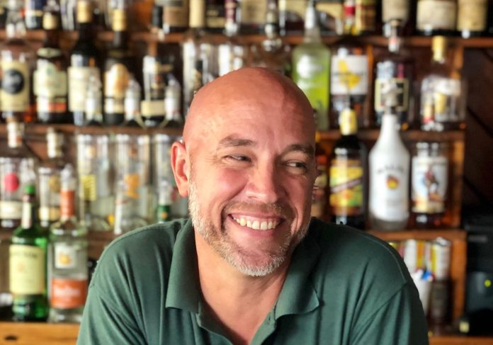 Bushey reflects on Key West, 20 years at Rick's - A man sitting at a table with wine glasses - Bartender