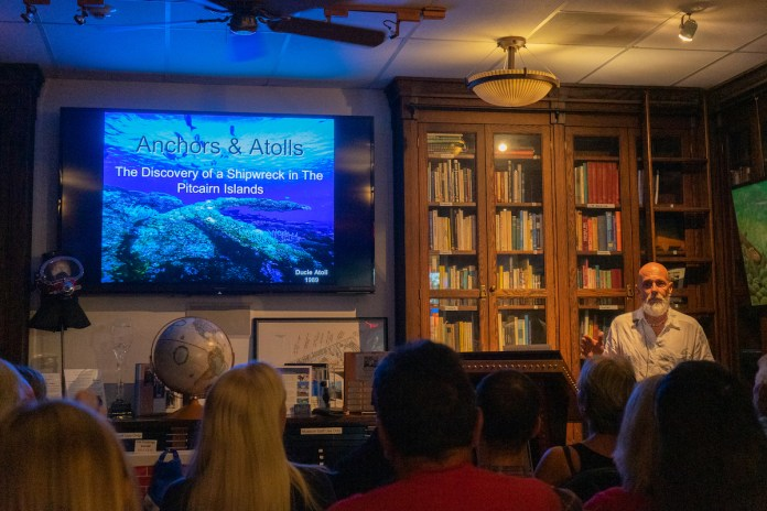 SHIPWRECKS AND SAILORS – Adventurous tale captivates crowd - A group of people standing in front of a television - Convention