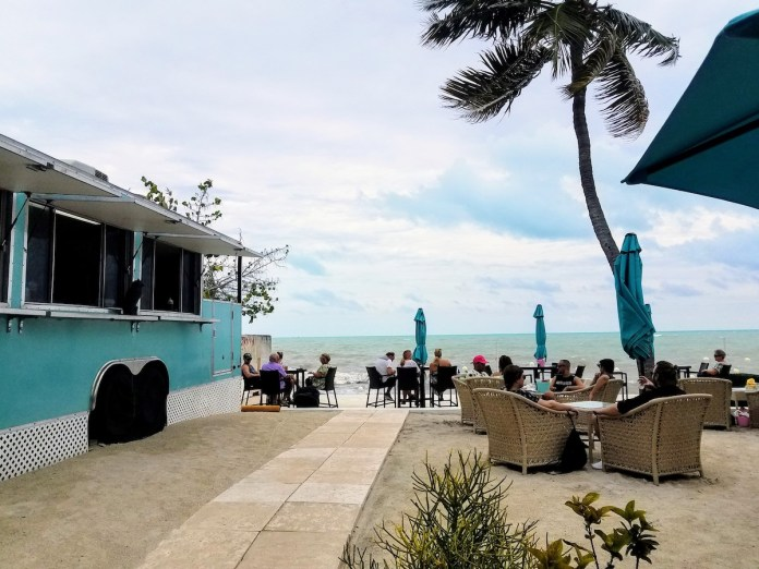 OFF THE PATH KEY – WEST'S SOUTHERNMOST HOUSE IS MORE THAN A MANSION - A group of people sitting at a bus stop - Palm trees