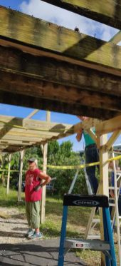 Guess what? Habitat is still helping homeowners recover from Irma - A group of people standing on top of a wooden bridge - Roof