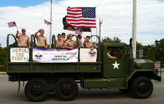 - A group of people riding on the back of a truck - Military Displays