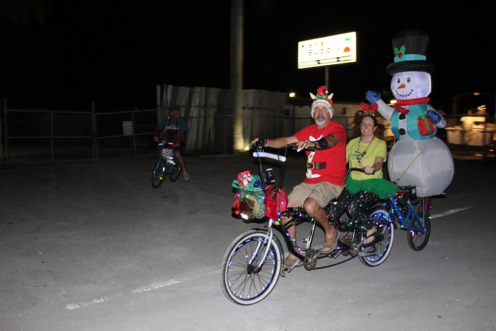 ROLLIN' INTO THE HOLIDAYS – Bike rides give back - A group of people riding on the back of a bicycle - Road bicycle