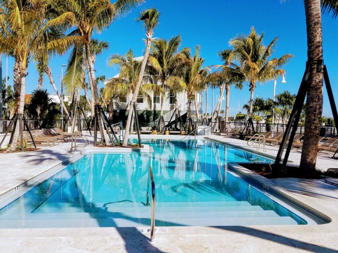It takes a village… - A group of palm trees next to a pool of water - Resort town