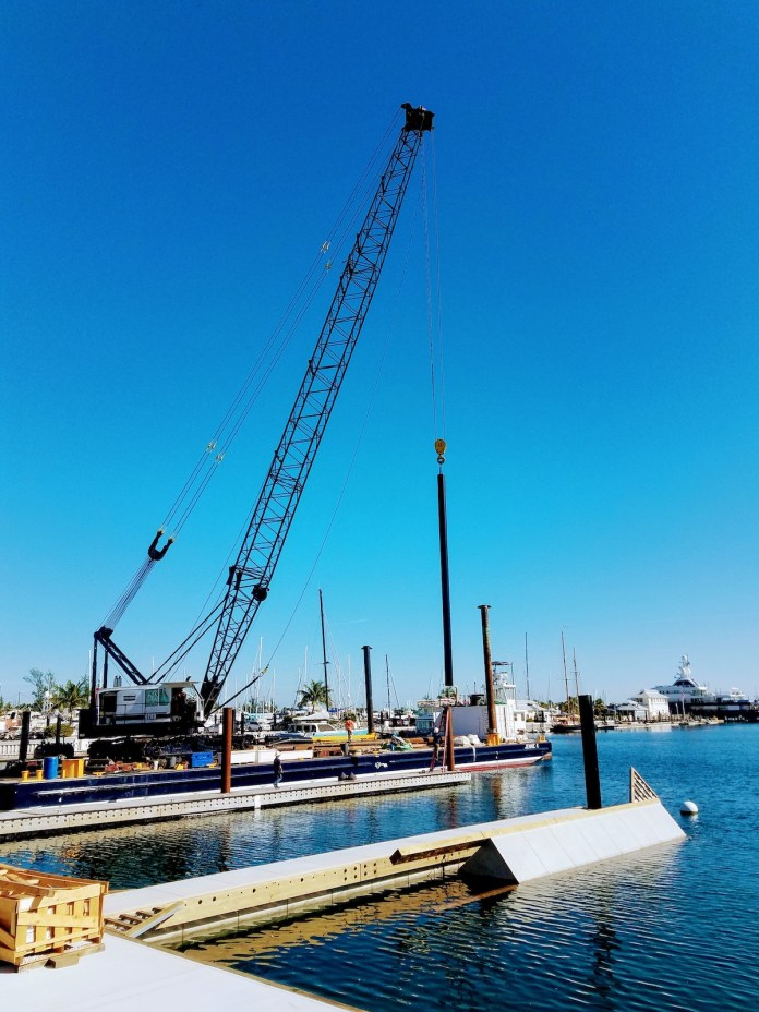 It takes a village… - A boat is docked next to a body of water - Crane vessel