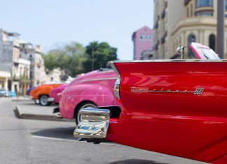 Learn about how to travel to Cuba at Marathon Library talk - A red car parked on the side of a road - Vintage car