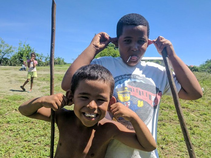 Learn about how to travel to Cuba at Marathon Library talk - A man and a little boy that is standing in the grass - Travel