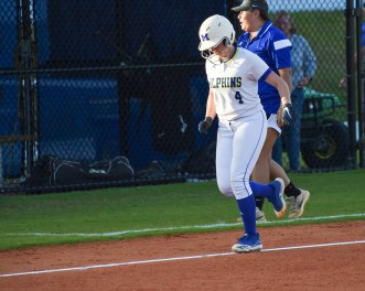 Lady Fin Cecily Ozbun rounds third and celebrates at home plate after hitting an over-the-fence home run in the third inning.