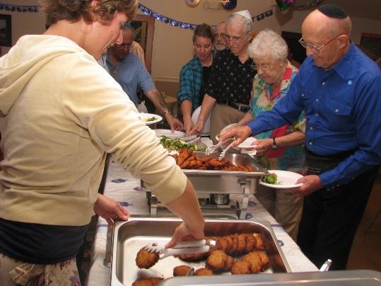Sarah Klitenick adds more Latkahs (potato pancakes) as CBZ members fill their plates