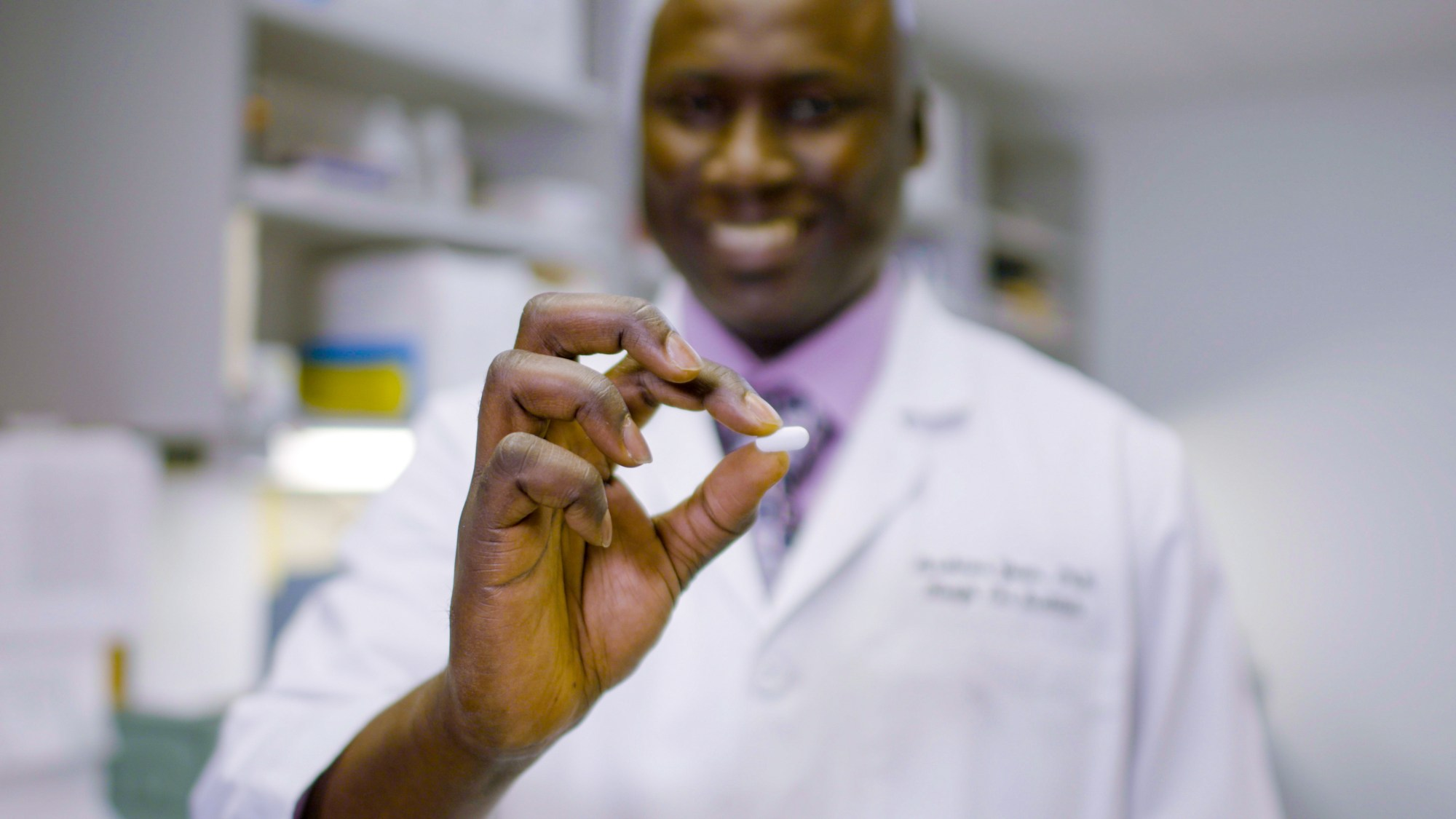 Ibrahima Youm, research scientist at HEI, holds the hearing loss pill
