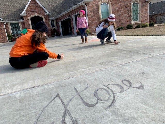 three young girls draw with chalk on driveway