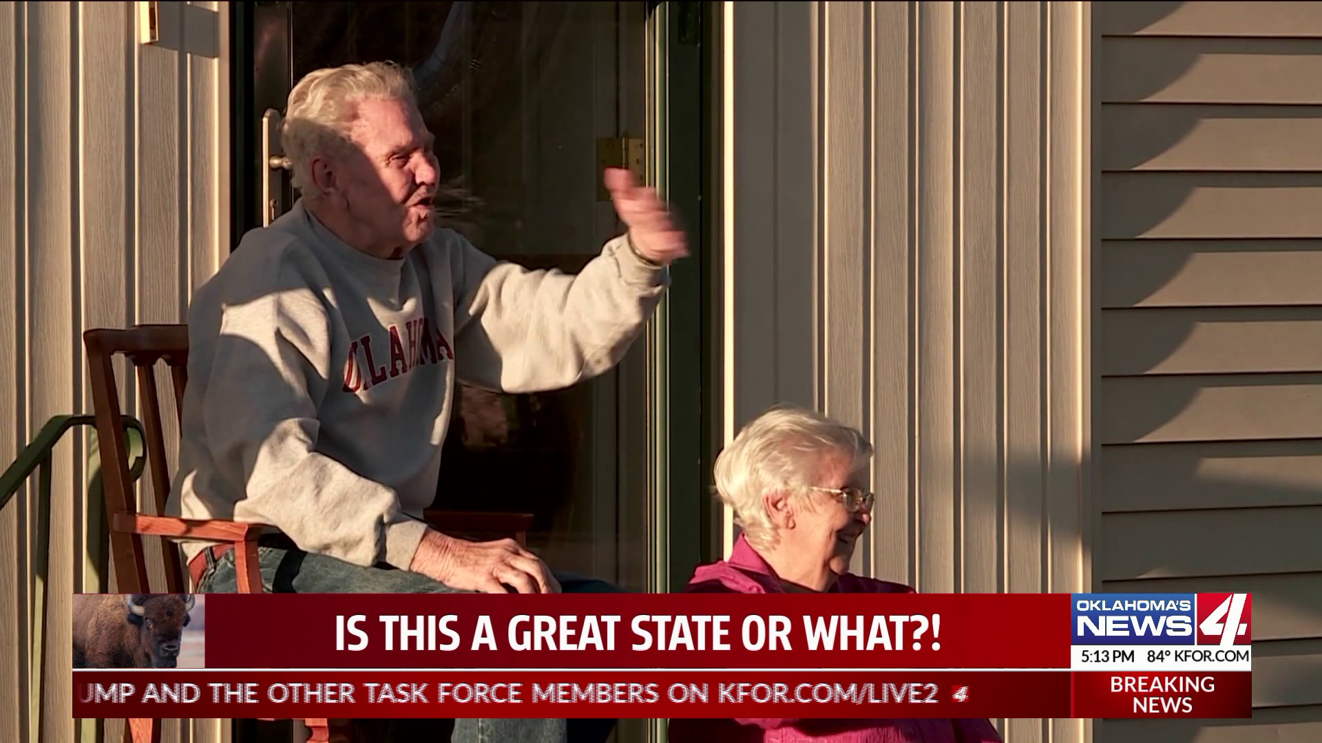 Elderly couple smiles and waves from porch