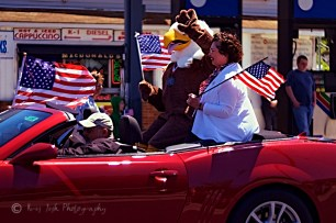 Mrs. Nancy Kelly, the sponsor of the Race for Cash which is run in memory for her son, Capt. Christopher Scott Cash who was killed in Baqubah, Iraq in 2004, rides in a convertible escorted by the race's new mascot, Spangle.