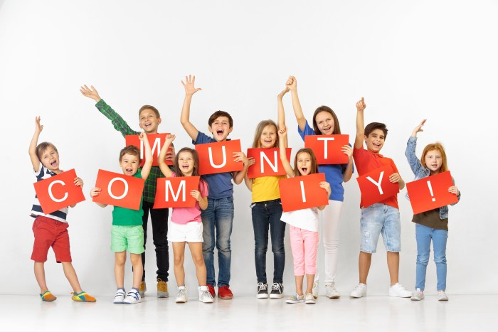 A selection of people and children each holding a letter of the word community