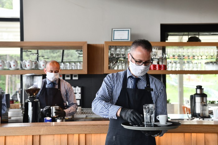 waiter in a medical protective mask serves the table in the restaurant