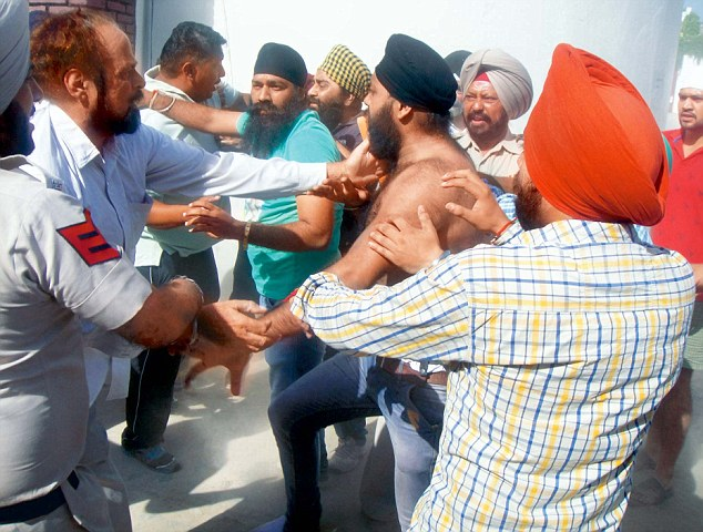 Sikh community members protest after a school management razed a portion of a gurdwara located on the Mission Road area in Pathankot on Saturday