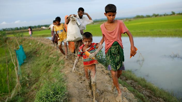 Rohingya refugees walk in a muddy road as they enter Bangladesh border in Teknaf, Bangladesh, 10 September 2017 (AAP)