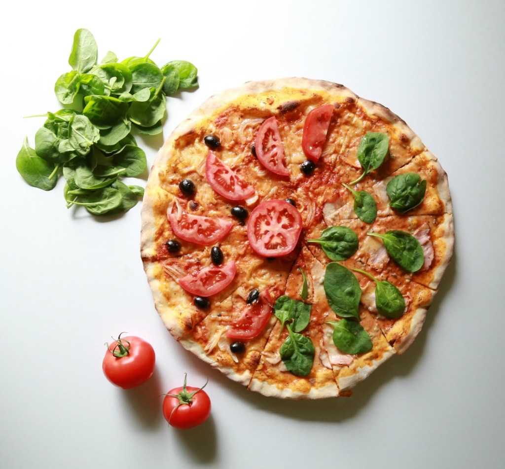 Image of pizza with spinach and tomatoes