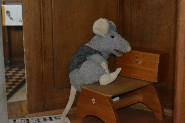 A couch mouse hiding behind the pulpit!