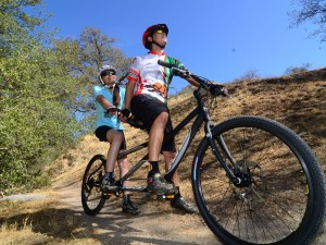 A couple riding a KHS Cross tandem in the hills