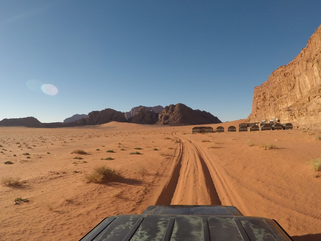 Photo of a jeep approaching desert camp in wadi rum