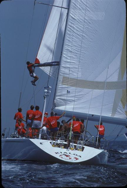 Kialoa V sailing with crew hanging from the spinnaker pole