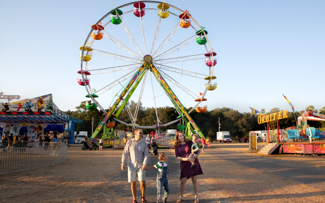 family walking in front of ferris wheel at Northwest Florida Fair
