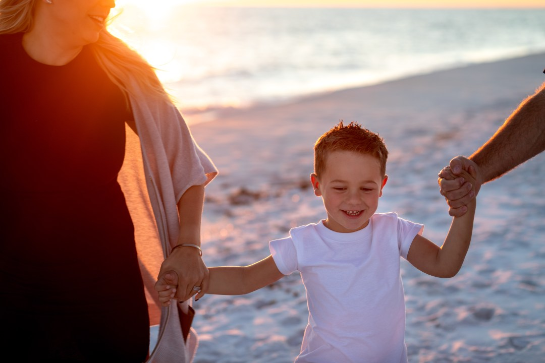 Okaloosa Island family photo of parents holding sons hand