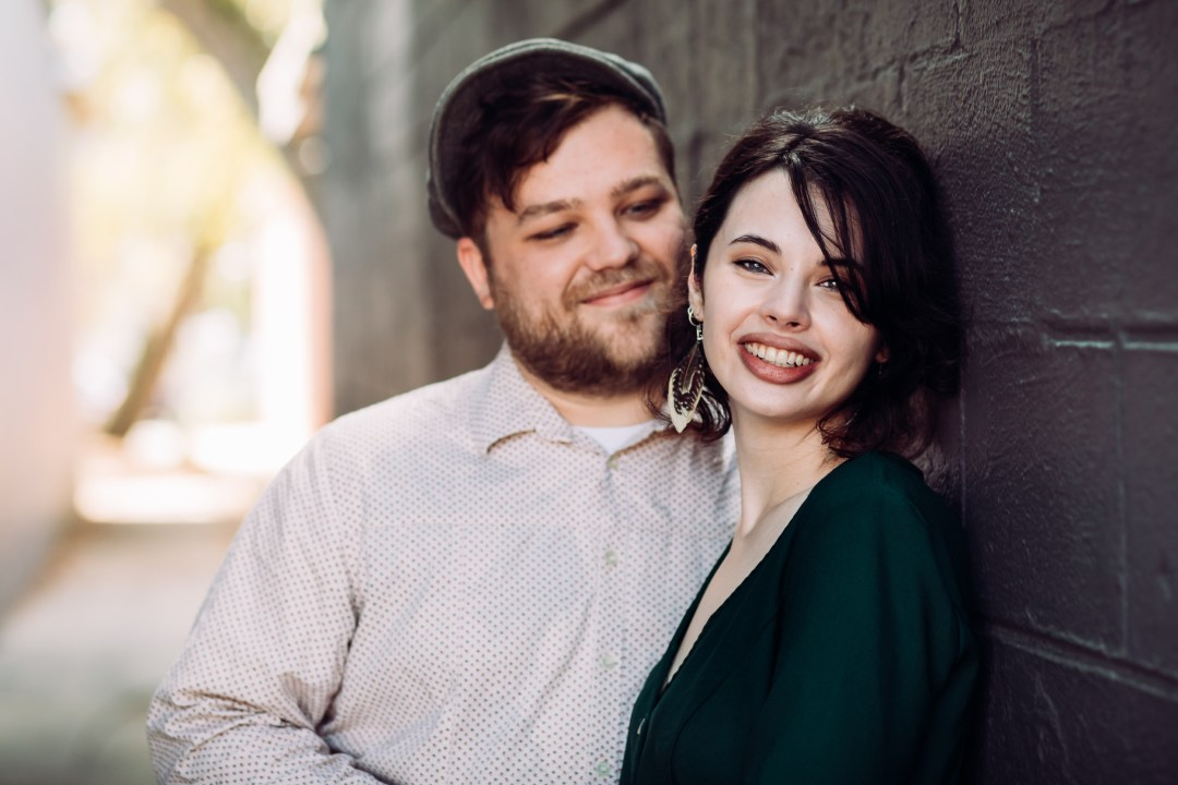 couple posing for anniversary photos in Fort Walton Beach downtown alley