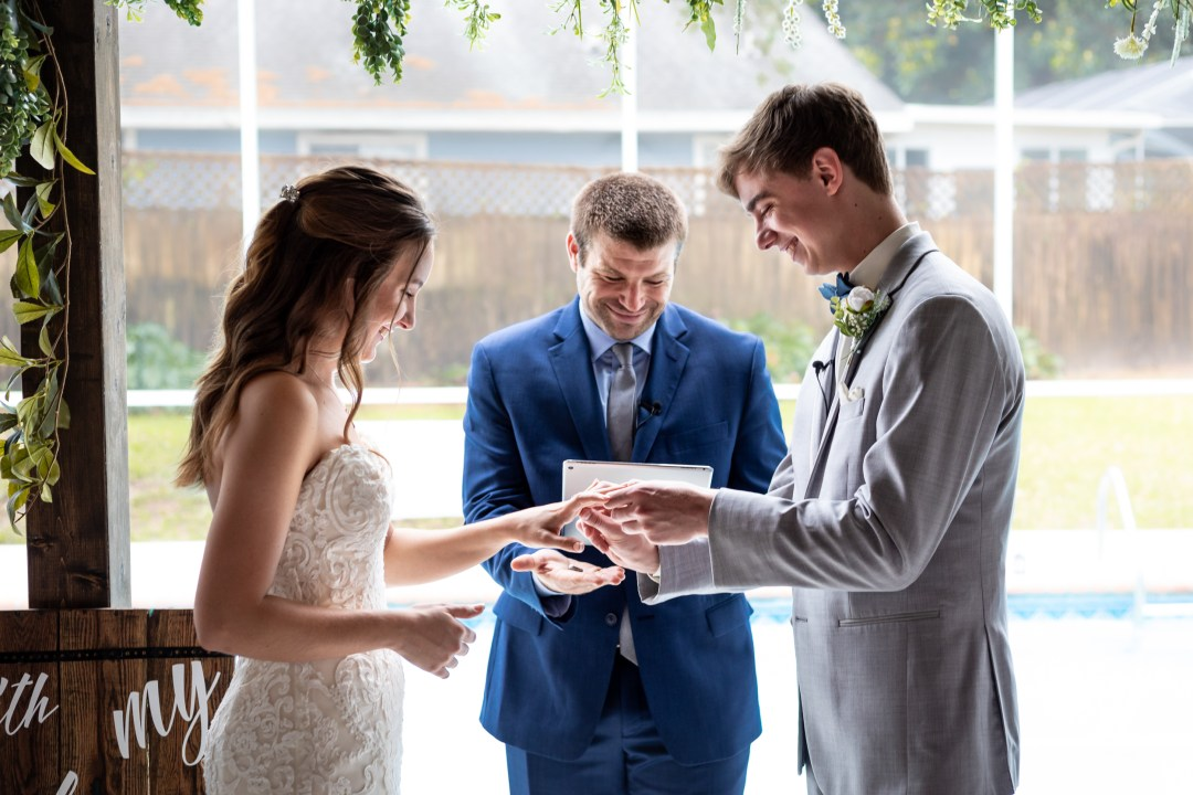 groom placing ring on bride during COVID-19 wedding video