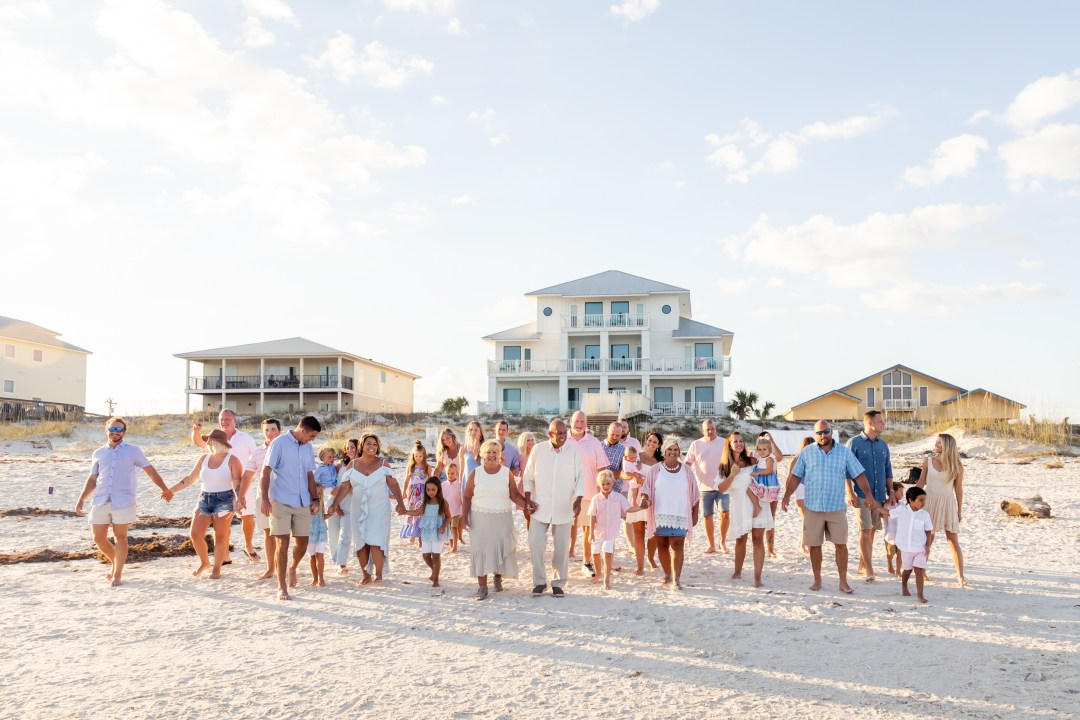 large family beach photo in front of best beach house in Gulf Shores