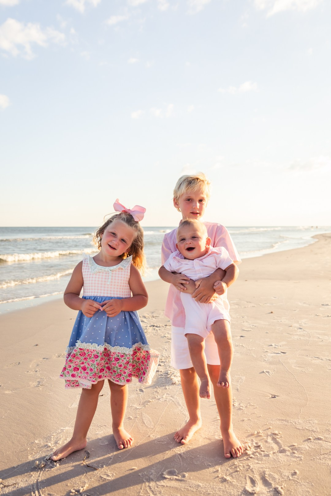 sister and two brothers posing for beach photos