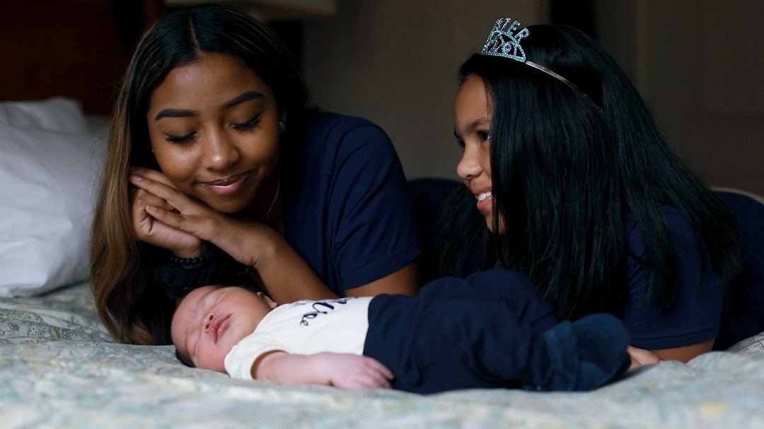 two sisters looking at newborn baby brother for maternity video