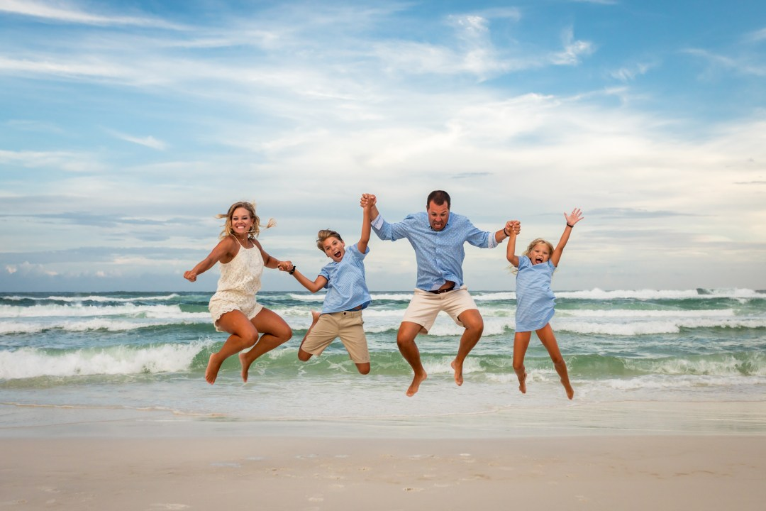 family jumping in the air on blue mountain beach