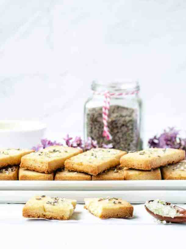 Lavender Lemon Shortbread Cookies stacked on two rectangular plates with a broken cookie in front and dried lavender in a jar behind vertical orientation