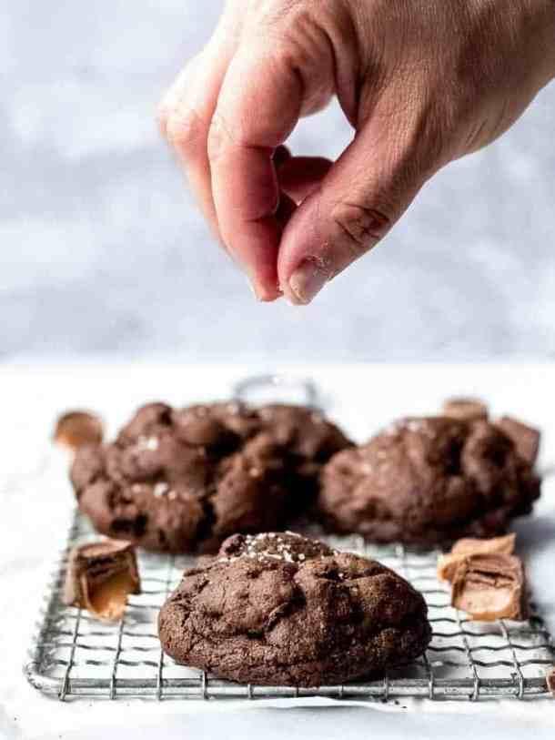 Salted Caramel Stuffed Dark Chocolate Cookies sprinkling salt onto cookie | kickassbaker.com