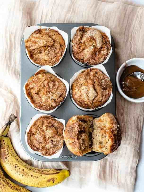 Overhead shot of 6 banana muffins in tin with one cut open to see dulce de leche swirled inside