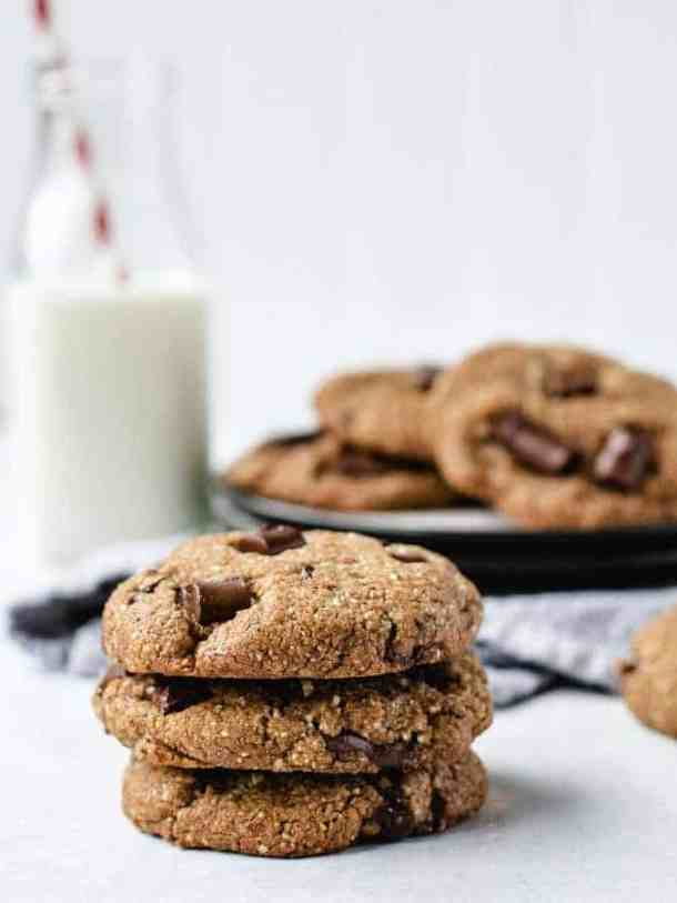 Stack of 3 paleo chocolate chip cookies with glass of milk behind